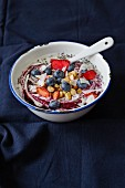 Coconut yogurt with blueberries, dried strawberries, roasted nuts and coconut chips