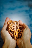 Hands holding crunchy sugar and cinnamon pretzels