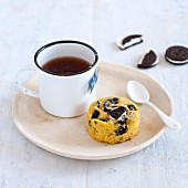 An Oreo cupcake with black tea