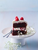 A piece of red velvet cake with raspberries on a cake stand
