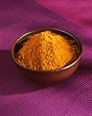 Currypulver im Schälchen auf pinkfarbener Tischdecke
