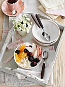 Bircher muesli with fresh fruit on a wooden breakfast tray