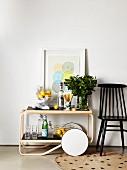 Klassiker-Servierwagen mit Zitronen, Getränkeflaschen, Blätterzweigen neben schwarzem Stuhl