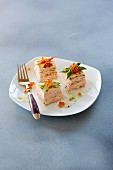 Crepe torte cubes with salmon and caviar on a plate