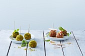 Various fresh cheese balls on plates with wooden skewers