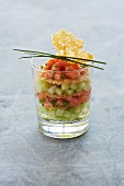 Salmon tartare served with cucumber cubes in a glass
