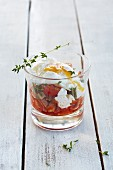 An appetiser with tomatoes, ham cubes and poached eggs in a glass