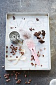 Chocolate drops, chocolate couverture, cocoa powder, a flour sieve, spoons and forks on a metal tray