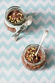 Two glasses of chocolate pudding with pistachios and spoons