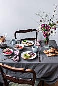 A breakfast table laid with millet porridge, spelt bagels, avocado, blueberries, pomegranate, cocoa beans and a flower bouquet