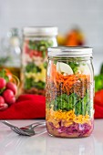 Layered salad in glass jars with spinach, carrots and cheese