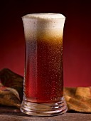 A glass of cold ale with foam on top