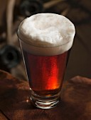 A glass of dark beer with foam