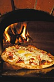 Pizza with fried eggs and prosciutto in front of a wood oven