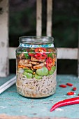 Miso soup in a glass jar with miso paste, soy noodles, beans, carrots, tofu, chilli and chopped spring onions