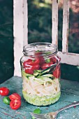 Tagliatelle with basil pesto, zucchini, cherry tomatoes and fresh basil in a glass jar