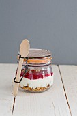 Banana granola in a jar with yoghurt and raspberry puree