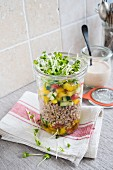 A buckwheat salad with vegetables and cress in a glass jar