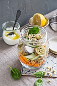 A vegetable salad with herb frittata rolls in a glass jar