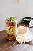 A pasta salad in a glass jar with tomatoes, olives and cheese