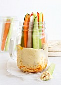 Vegetable sticks in a glass jar with houmous