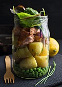 Steamed salmon and potatoes in a glass jar with peas and chard