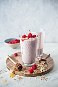Breakfast smoothies with raspberries, yoghurt, milk, honey, oatmeal and linseed in glasses