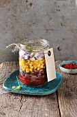Layered salad with beans, corn and red onion in a glass