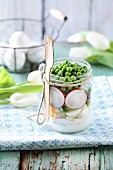 A spring salad in a glass jar with peas, radishes and egg