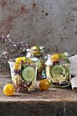 Hirsesalat im Glas mit Gurke, gelben Kirschtomaten und Rotkohl