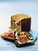 Selbstgebackenes Brot belegt mit Frischkäse, Schinken und Grillgemüse