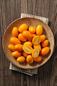 Fresh kumquats in a wooden bowl (top view)
