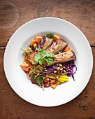 Marinated pork belly with a vegetable salad, papaya and peanuts
