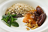 Yoghurt with dates, chia seeds, oatmeal, nuts, fruit sauce and mint