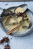 A plate with cookie cutters, a spoon, sugar, star anise and a cinnamon stick
