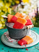 Mixed melon ice lollies in an ice bucket