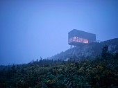 Modernes Kubus-Haus ragt über einen Abhang in den Nebel