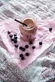 A vegan blueberry and yoghurt smoothie in a glass jar