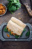 A vegan shredded jackfruit sandwich with spinach and cabbage