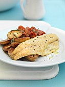 Sea bass with fried potatoes and tomatoes