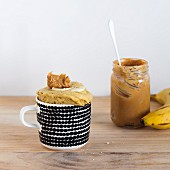 Banana bread mug cake with a jar of peanut butter