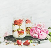 Greek yogurt, granola, strawberry breakfast in glass jars, pink raninkulus flowers, marble background