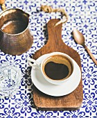 Cup of black Eastern style coffee on wooden serving board over oriental bright motley Moroccan patterned background