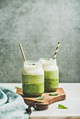 Ombre layered green smoothies with mint in glass jars with straws on wooden board, grey concrete wall background