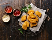 Chicken breast nuggets with popular sauces for choice on wire rack on wooden background