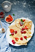 Crepes topped with cream, berries, icing sugar