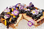 Blueberry cheese cake on a glass cake stand decorated with Pansy flowers and Marigold petals