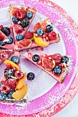 Overhead view of strawberry cheesecake slices on three pink and red plates topped with fresh fruit and rasberry coulis