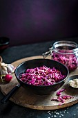 Home made red cabbage kimchi in a bowl, jar in the background