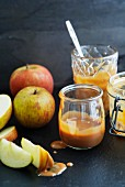 Caramel sauce in jam jars with whole and sliced apples